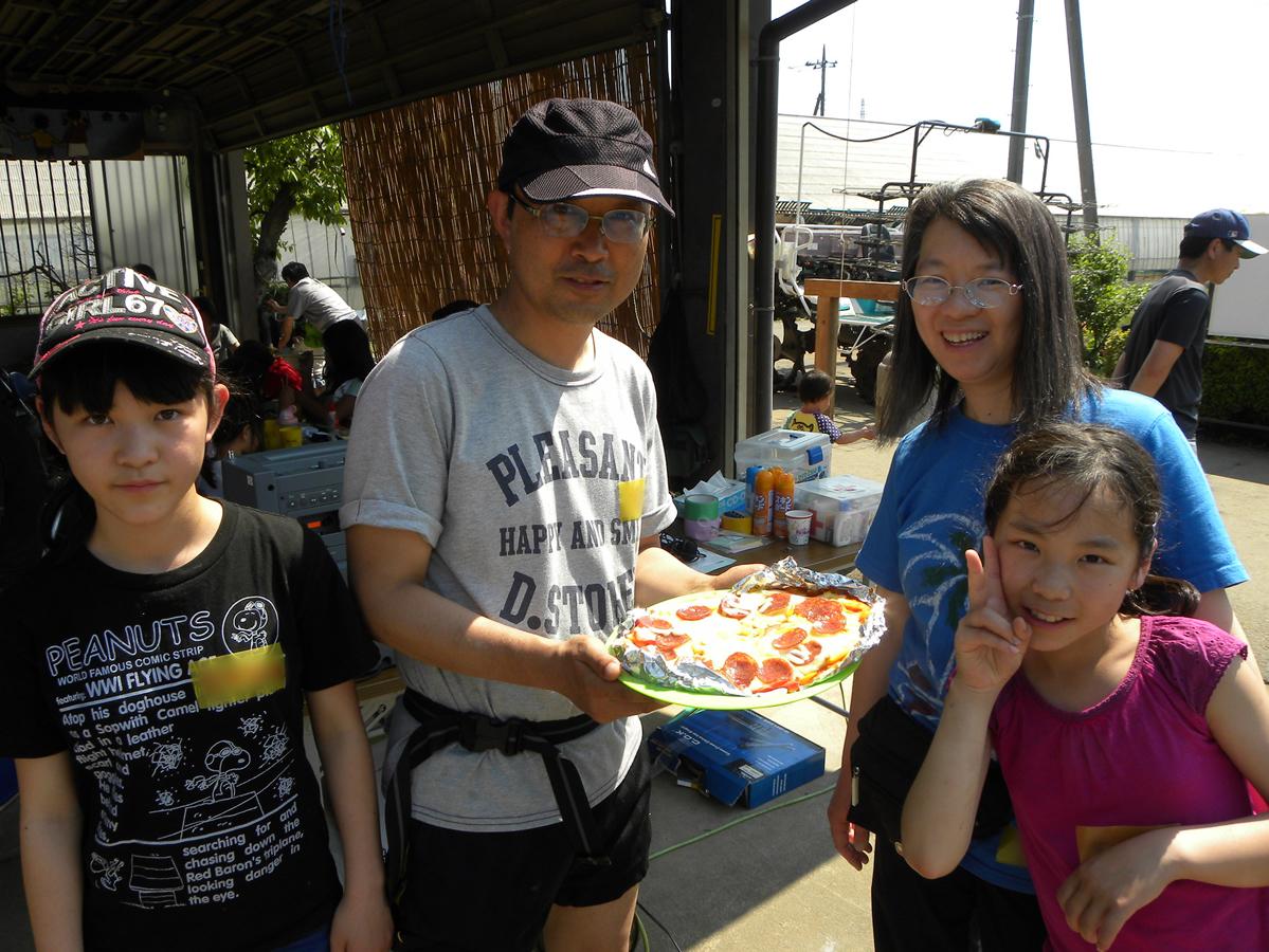 焼き上がったピザを盛った家族の写真