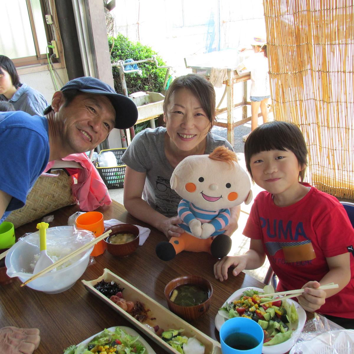 ほぺたん人形と一緒に家族で食事している写真