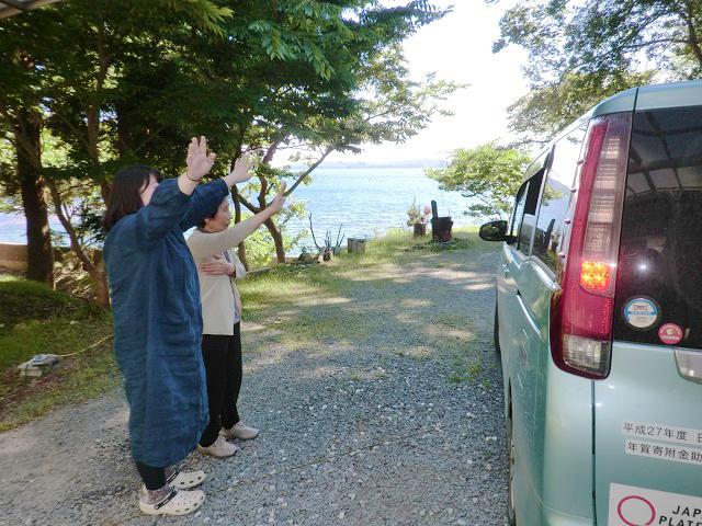 ▲サロン終了後、送迎車を見送る参加者とスタッフ。庭の向こうには牡鹿の海が広がっています。